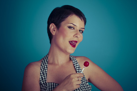 sugarplum: Sugarplum, happy young woman with lollypop  in her mouth on blue background