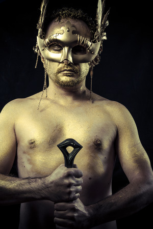 ancient sexy: Warrior with helmet and sword with his body painted gold dust
