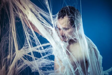 naked man: Tangled, naked man trapped in a huge spider web Stock Photo