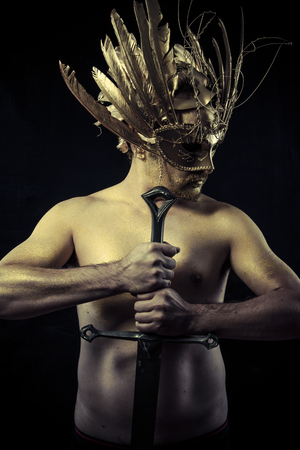 legend: Legend, Warrior with helmet and sword with his body painted gold dust Stock Photo