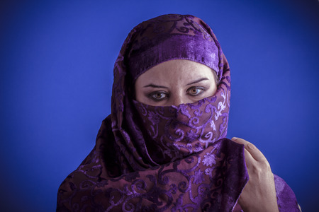 Beautiful arabic woman with traditional veil on her face, intense look Stock Photo