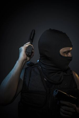 red handed: Man wearing balaclavas and bulletproof vest with firearms
