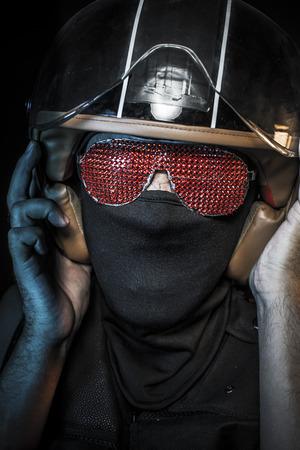 casco rojo: motorista con las gafas de sol de cristales rojos y pasamontañas