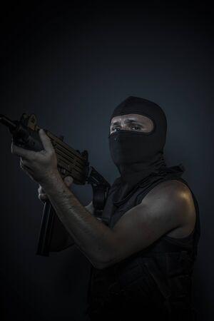 bulletproof vest: Man wearing balaclavas and bulletproof vest with firearms