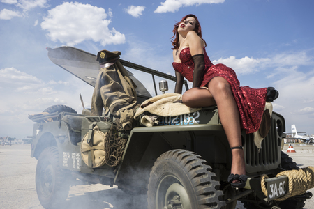 Aviation, pinup dressed in era of the Second World War on a military jeep