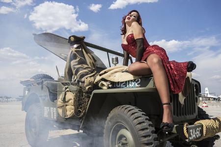 Aviation, pinup gekleed in de tijd van de Tweede Wereldoorlog op een militaire jeep Stockfoto - 48441581