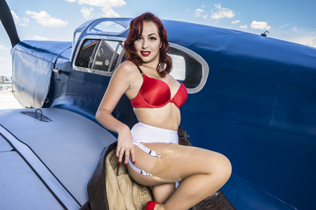 Sexy, beautiful woman with pinup style of the Second World War, along with vintage aircraft Stock Photo