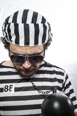 Desperate, portrait of a man prisoner in prison garb, over white background Stock Photo