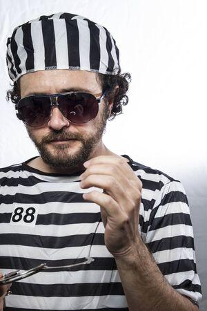 imprisoned person: Desperate, portrait of a man prisoner in prison garb, over white background Stock Photo