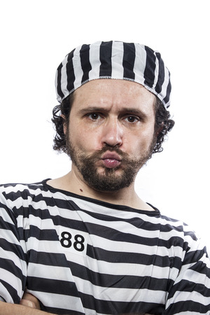garb: Illegal, Desperate, portrait of a man prisoner in prison garb, over white background Stock Photo