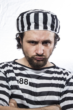incarcerated: Desperate, portrait of a man prisoner in prison garb, over white background Stock Photo