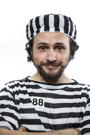 detained: Illegal, Desperate, portrait of a man prisoner in prison garb, over white background Stock Photo