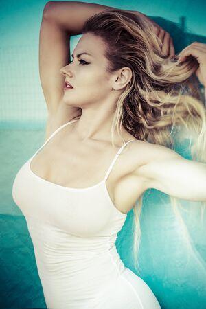 Sommer, schöne Blondine kleidete in der weißen Hemdstrandumwelt an