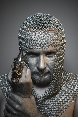 medieval sword: Protection, man in chain mail and leather painted silver, medieval warrior