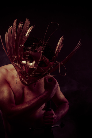 gold dust: Fighter, warrior with golden mask and huge iron sword, body covered with gold dust Stock Photo