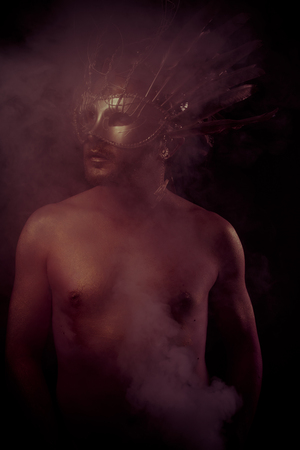 gold dust: Spartan, warrior with golden mask and huge iron sword, body covered with gold dust Stock Photo