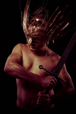 sexy male model: Spartan, warrior with golden mask and huge iron sword, body covered with gold dust Stock Photo