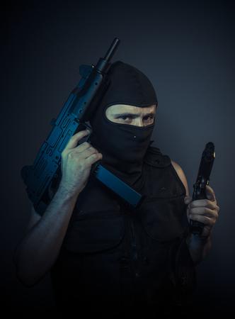 assassin: Assassin, terrorist carrying a machine gun and balaclava Stock Photo