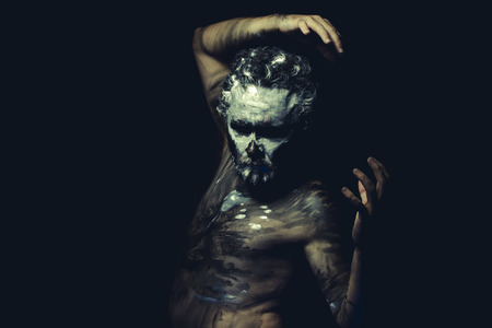 tribu: Aborigen, salvaje con la cara pintada de blanco y el cuerpo lleno de pintura negro Foto de archivo