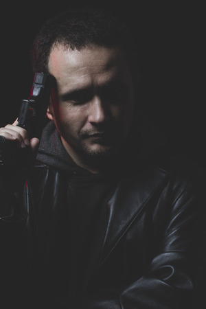 intent: Depressed, Man with intent to commit suicide, gun and leather jacket, red backlight