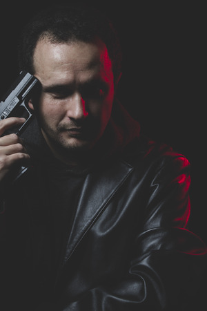 commit: Unhappy, Man with intent to commit suicide, gun and leather jacket, red backlight