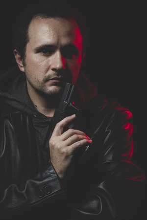 intent: Shoot, Man with intent to commit suicide, gun and leather jacket, red backlight Stock Photo