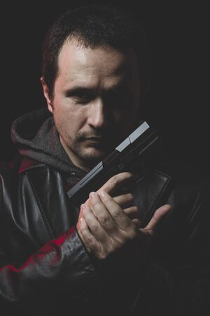 intent: Sadness, Man with intent to commit suicide, gun and leather jacket, red backlight