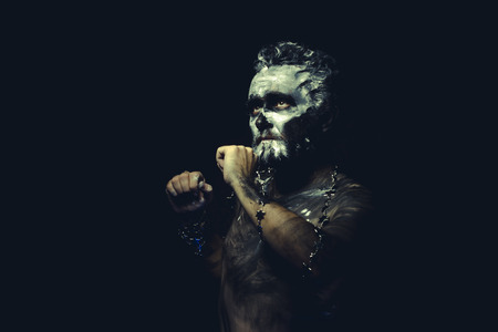 african warriors: wild man with white painted face and full body black paint