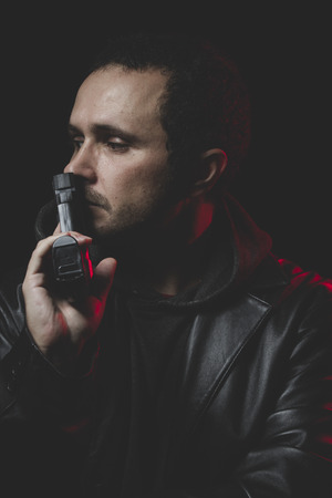 commit: Unhappy, Man with intent to commit suicide, gun and leather jacket, red backlightUnhappy, Man with intent to commit suicide, gun and leather jacket, red backlight Stock Photo