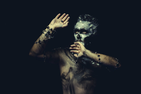 painted face: wild man with white painted face and full body black paint