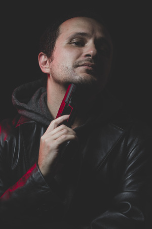 to commit: Man with intent to commit suicide, gun and leather jacket, red backlight