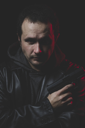 commit: Depressed, Man with intent to commit suicide, gun and leather jacket, red backlight