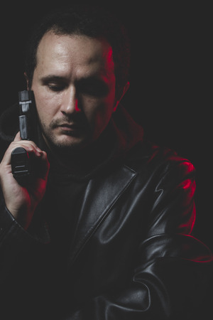 commit: Problem, Man with intent to commit suicide, gun and leather jacket, red backlight