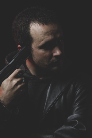 death head holding: Man with intent to commit suicide, gun and leather jacket, red backlight