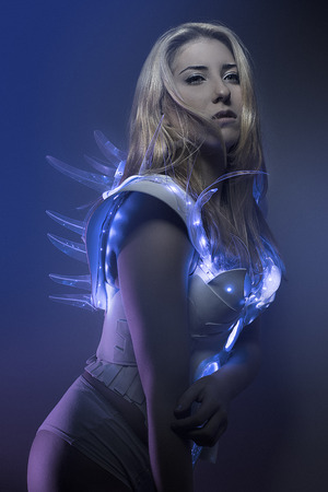 astronauts: blonde girl with white robot suit and blue LED lights Stock Photo