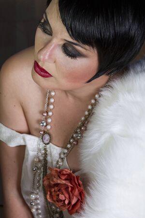 flapper: Hermosa morena sola aleta estilo 20s chica con joyas y piel blanca Foto de archivo
