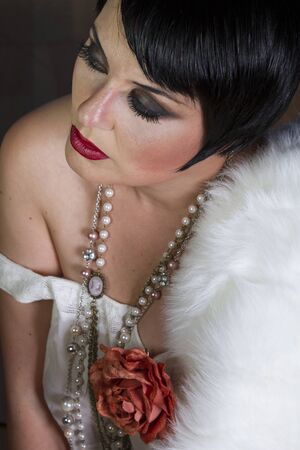 20s: Single beautiful brunette girl 20s style flapper with jewels and white fur