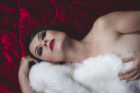 Sexy chica morena hermosa con el pelo corto acostado en una tela de color rojo oscuro Foto de archivo - 76727718