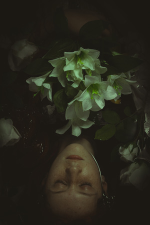 youth crime: Innocence, Teen submerged in water with white roses, romance scene Stock Photo