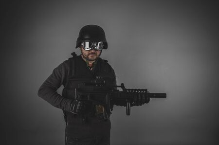 airsoft: forces, airsoft player with gun, helmet and bulletproof vest on gray background