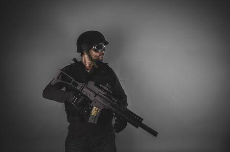 bulletproof vest: airsoft player with gun, helmet and bulletproof vest on gray background