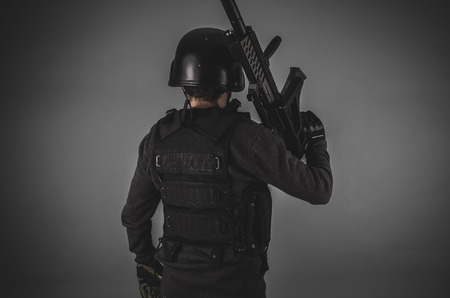 bulletproof vest: forces, airsoft player with gun, helmet and bulletproof vest on gray background