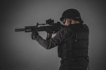 bulletproof vest: shooting, airsoft player with gun, helmet and bulletproof vest on gray background