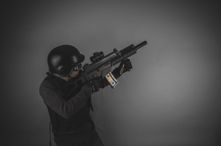 airsoft gun: airsoft player with gun, helmet and bulletproof vest on gray background