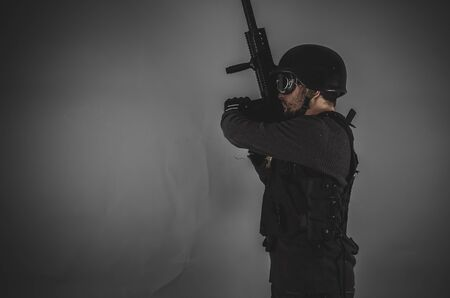 airsoft gun: guard, airsoft player with gun, helmet and bulletproof vest on gray background