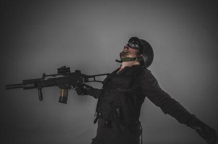 bulletproof vest: war airsoft player with gun, helmet and bulletproof vest on gray background Stock Photo
