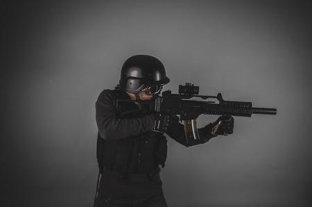bulletproof vest: sniper, airsoft player with gun, helmet and bulletproof vest on gray background