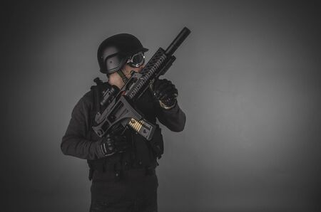 airsoft gun: aiming, airsoft player with gun, helmet and bulletproof vest on gray background Stock Photo