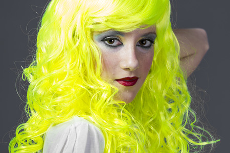 color model: teenager with fluorescent yellow wig, carrying a cardboard write message Stock Photo