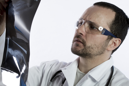 x ray equipment: Radiologist looking at an x-ray in hospital